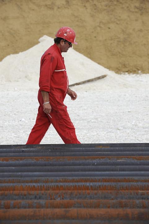 photo fred bourcier ouvrier et tubes acier forages sur site de forage pétrolier